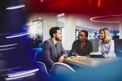 Business man and women in an office having a meeting. Primary colors: blue, red and turquoise.